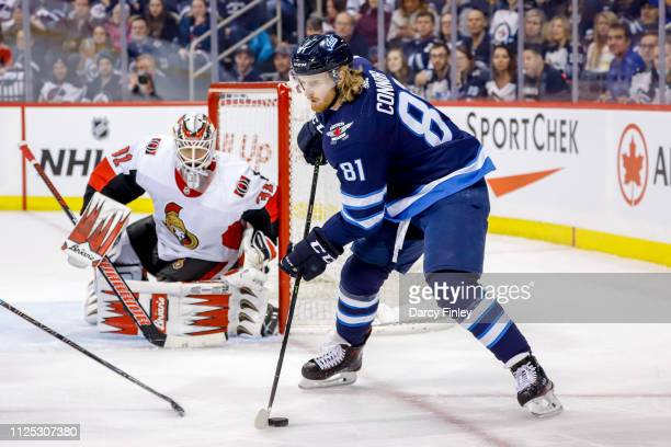 Goaltender Anders Nilsson of the Ottawa Senators keeps an eye on Kyle Connor of the Winnipeg Jets as he plays the puck during first period action at...