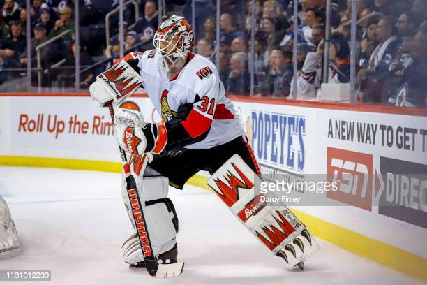 Goaltender Anders Nilsson of the Ottawa Senators plays the puck behind the net during the overtime period against the Winnipeg Jets at the Bell MTS...