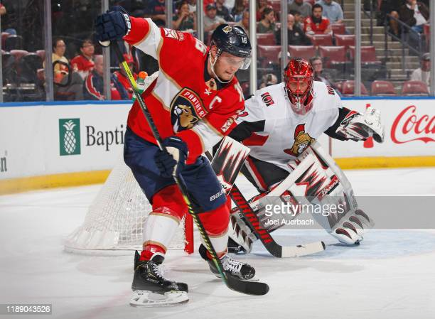Goaltender Anders Nilsson of the Ottawa Senators watches Aleksander Barkov of the Florida Panthers as he attempts to gain control of the puck during...