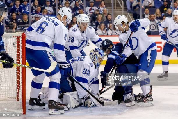 Goaltender Andrei Vasilevskiy of the Tampa Bay Lightning covers the puck in the crease while teammates Anton Stralman Mikhail Sergachev and Brayden...