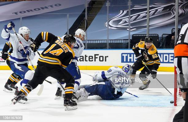 Goaltender Andrei Vasilevskiy of the Tampa Bay Lightning looks back at the puck sliding toward the goal line as Chris Wagner and Sean Kuraly of the...