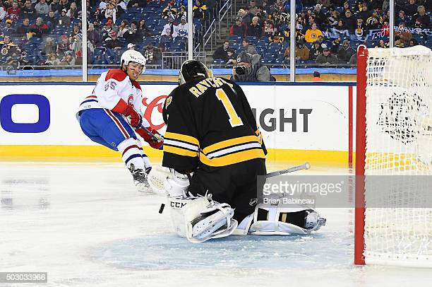 Goaltender Andrew Raycroft of the Boston Bruins Alumni Team makes a save on Francis Bouillon of the Montreal Canadiens Alumni Team during the Alumni...