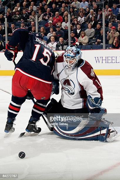 Goaltender Andrew Raycroft of the Colorado Avalanche makes a save as Derek Dorsett of the Columbus Blue Jackets battles for position in front of the...
