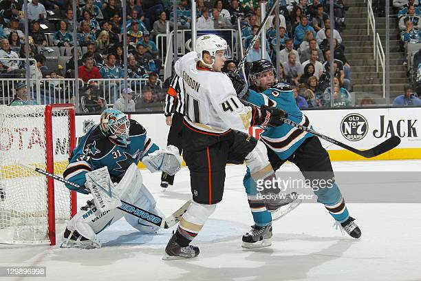 Goaltender Antii Niemi and defenseman Colin White of the San Jose Sharks battle to defend the net against right wing Andrew Gordon of the Anaheim...