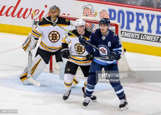 Goaltender Anton Khudobin Torey Krug of the Boston Bruins and Mark Scheifele of the Winnipeg Jets keep an eye on the play at the point during second...