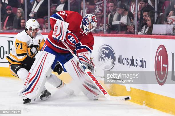 Goaltender Antti Niemi of the Montreal Canadiens tries to clear the puck with Evgeni Malkin of the Pittsburgh Penguins challenging from behind during...