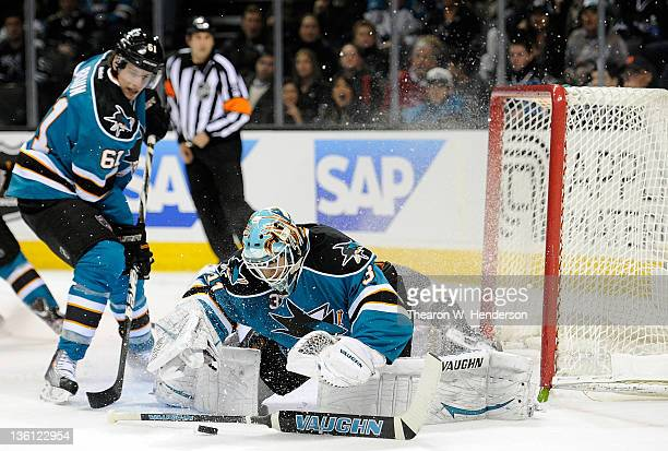 Goaltender Antti Niemi of the San Jose Sharks dives to stop the puck headed for his goal as teammate Justin Braun looks on against the Anaheim Ducks...