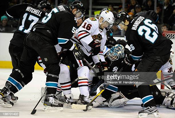 Goaltender Antti Niemi of the San Jose Sharks gets help from teammates Michal Handzus Colin White and Torrey Mitchell in stopping the rebound shot of...