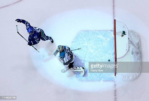 Goaltender Antti Niemi of the San Jose Sharks looks on as Daniel Sedin of the Vancouver Canucks celebrates after a deflection for a goal by Ryan...