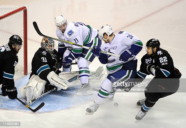 Goaltender Antti Niemi of the San Jose Sharks makes a save on a scoring attempt on the rebound from Jannik Hansen of the Vancouver Canucks in the...