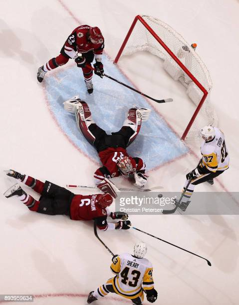 Goaltender Antti Raanta of the Arizona Coyotes makes a save on the puck as Sidney Crosby of the Pittsburgh Penguins attempts to shoot on the rebound...