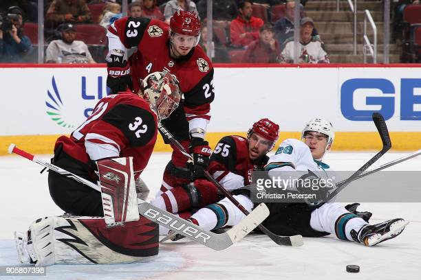 Goaltender Antti Raanta of the Arizona Coyotes makes a save on the puck as Timo Meier of the San Jose Sharks Oliver EkmanLarsson and Jason Demers...