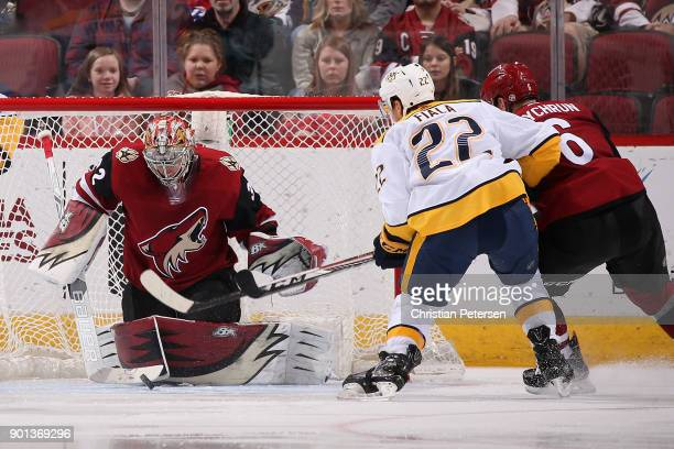Goaltender Antti Raanta of the Arizona Coyotes makes pad save on the puck as Kevin Fiala of the Nashville Predators skates in during the third period...