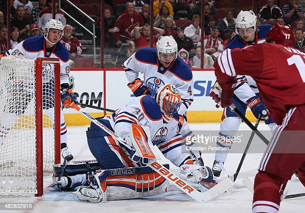 Goaltender Ben Scrivens of the Edmonton Oilers covers the puck after making a save against the Phoenix Coyotes during the first period of the NHL...