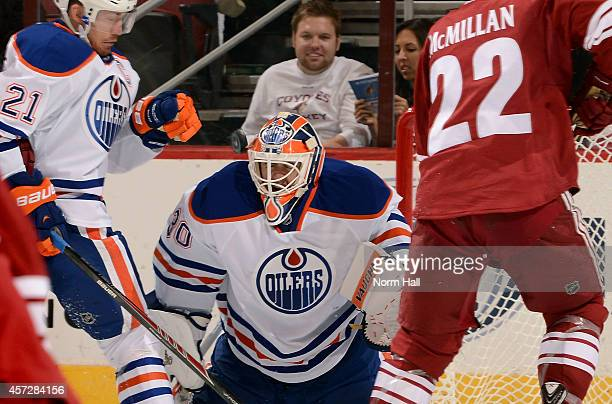 Goaltender Ben Scrivens of the Edmonton Oilers is hit in the helmet by a shot on goal between defenseman Andrew Ference of the Oilers and Brandon...