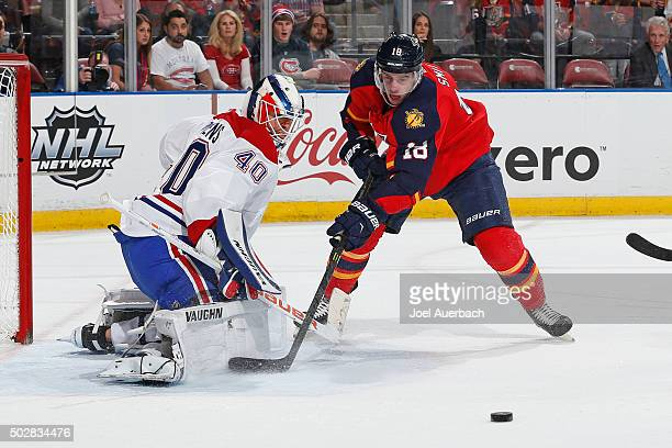 Goaltender Ben Scrivens of the Montreal Canadiens deflects the shot by Reilly Smith of the Florida Panthers during first period action at the BBT...