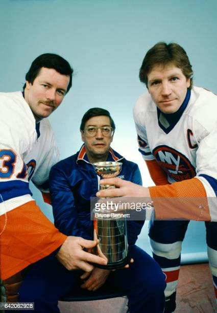 Goaltender Billy Smith head coach Al Arbour and Denis Potvin of the New York Islanders hold up a replica of the Stanley Cup Trophy circa February...