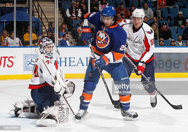 Goaltender Braden Holtby of the Washington Capitals defends the net as teammate Jeff Schultz and Matt Moulson of the New York Islanders look for the...