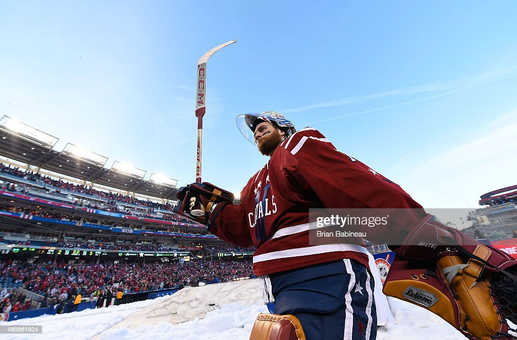 Goaltender Braden Holtby #70 of the Washington Capitals raises his stick in the air to acknowledge the fans after the 2015 Bridgestone NHL Winter Classic at Nationals Park on January 1, 2015 in Washington, D.C. The Capitals defeated the Blackhawks 3-2.