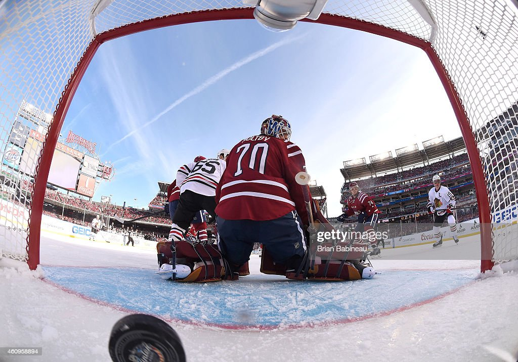 Goaltender Braden Holtby #70 of the Washington Capitals reacts after a goal by Patrick Sharp #10 of the Chicago Blackhawks (not in photo) as Jonathan Toews #19 of the Chicago Blackhawks looks at the puck in the net during the first period of the 2015 Bridgestone NHL Winter Classic at Nationals Park on January 1, 2015 in Washington, D.C.
