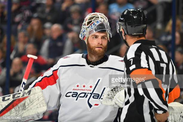 Goaltender Braden Holtby of the Washington Capitals talks with referee Garrett Rank during a time out in the third period against the Columbus Blue...