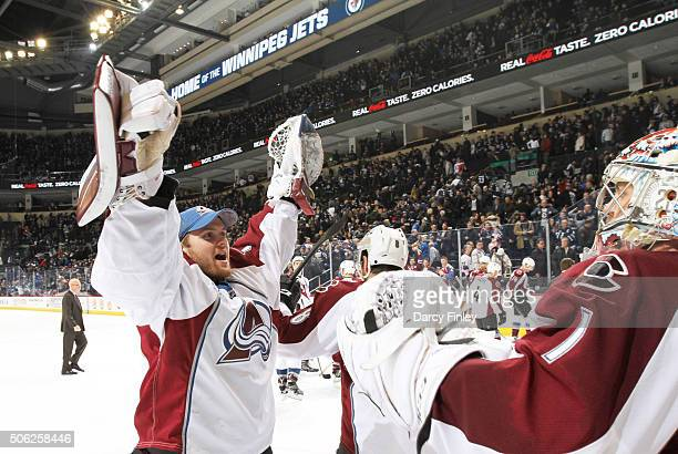 Goaltender Calvin Packard of the Colorado Avalanche raises his arms in celebration as he congratulates teammate Semyon Varlamov following a 21...