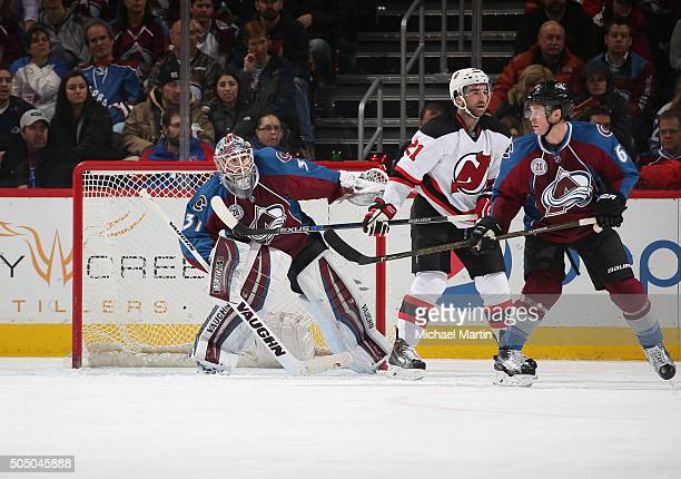 Goaltender Calvin Pickard of the Colorado Avalanche looks around teammate Chris Wagner and Kyle Palmieri of the New Jersey Devils at the Pepsi Center...