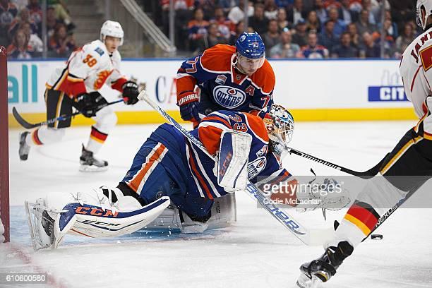 Goaltender Cam Talbot of the Edmonton Oilers makes a save against Mark Jankowski of the Calgary Flames as Oscar Klefbom of the Oilers looks on on...