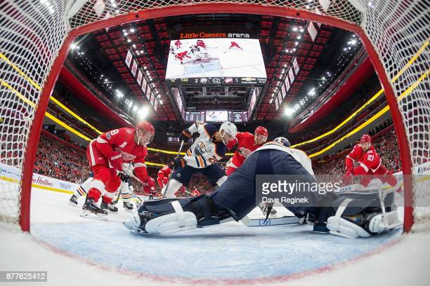 Goaltender Cam Talbot of the Edmonton Oilers reaches for the puck from Tomas Tatar of the Detroit Red Wings who looks to score while Darnell Nurse of...