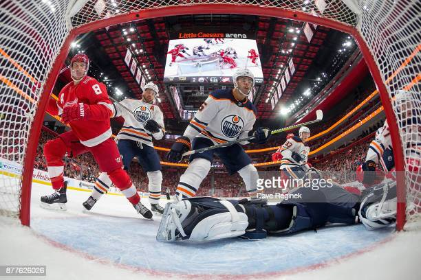 Goaltender Cam Talbot of the Edmonton Oilers reaches for the puck while teammates Darnell Nurse and Adam Larsson defend against Justin Abdelkader of...