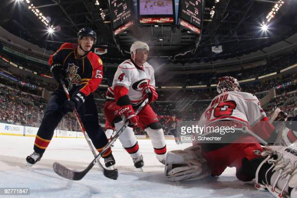 Goaltender Cam Ward of the Carolina Hurricanes defends the net with teammate Aaron Ward against Rostislav Olesz of the Florida Panthers at the...