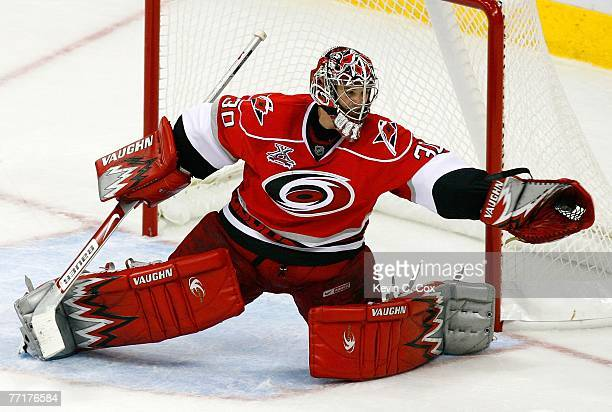 Goaltender Cam Ward of the Carolina Hurricanes saves a shot on goal with his glove during the third period against the Montreal Canadiens October 3...