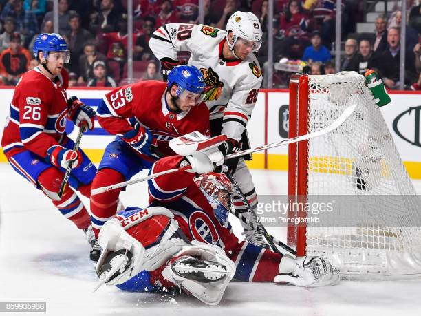 Goaltender Carey Price of the Montreal Canadiens covers the puck with his glove while teammate Victor Mete defends against Brandon Saad of the...