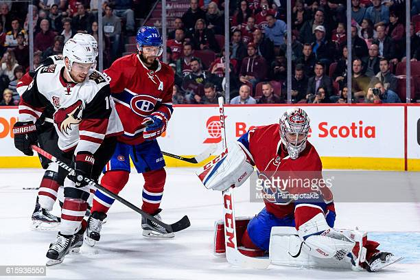 Goaltender Carey Price of the Montreal Canadiens gloves the puck near Max Domi of the Arizona Coyotes during the NHL game at the Bell Centre on...
