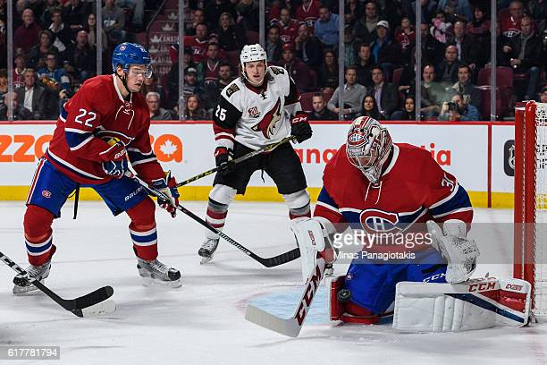 Goaltender Carey Price of the Montreal Canadiens makes a save near teammate Mikhail Sergachev and Ryan White of the Arizona Coyotes during the NHL...