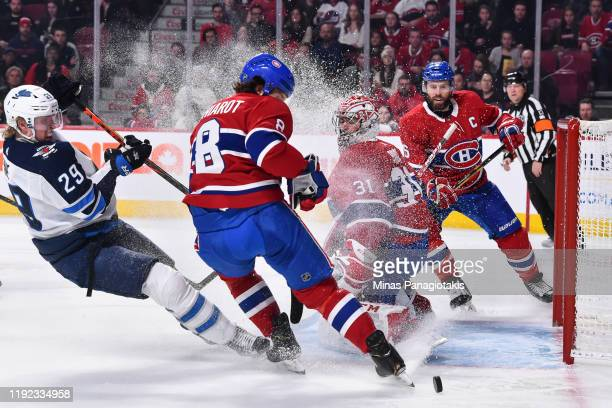 Goaltender Carey Price of the Montreal Canadiens protects the net against the puck while teammate Ben Chiarot defends against Patrik Laine of the...