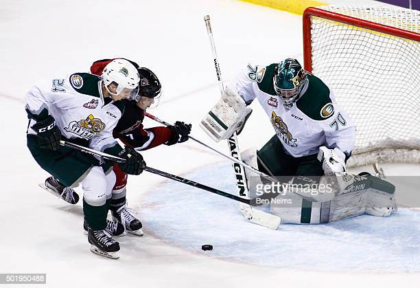 Goaltender Carter Hart of the Everett Silvertips makes a save against Ty Ronning of the Vancouver Giants near teammate Lucas Skrumeda during the...