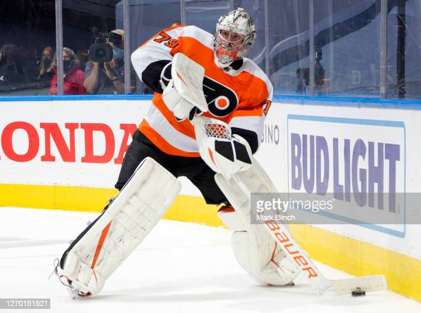 Goaltender Carter Hart of the Philadelphia Flyers plays the puck against the New York Islanders during the second period of Game Five of the Eastern...