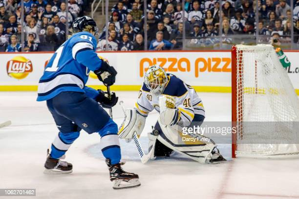 Goaltender Carter Hutton of the Buffalo Sabres makes a pad save on Kyle Connor of the Winnipeg Jets during the overtime period at the Bell MTS Place...
