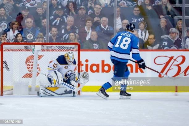 Goaltender Carter Hutton of the Buffalo Sabres makes a save against Bryan Little of the Winnipeg Jets during the shootout at the Bell MTS Place on...