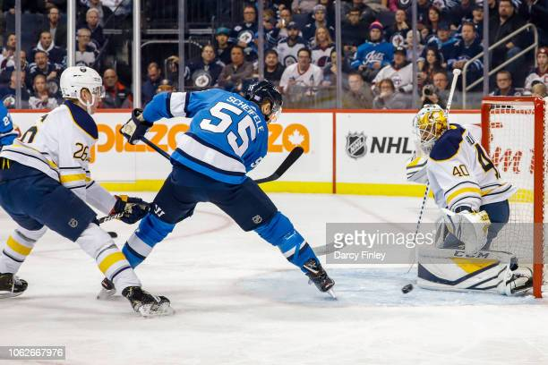 Goaltender Carter Hutton of the Buffalo Sabres makes a save on a deflection by Mark Scheifele of the Winnipeg Jets during first period action at the...