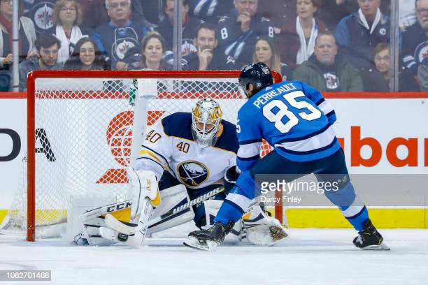 Goaltender Carter Hutton of the Buffalo Sabres makes a save on Mathieu Perreault of the Winnipeg Jets during the shootout at the Bell MTS Place on...