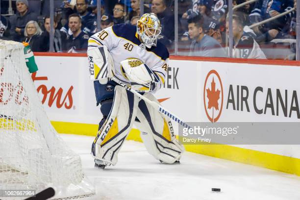 Goaltender Carter Hutton of the Buffalo Sabres plays the puck behind the net during first period action against the Winnipeg Jets at the Bell MTS...
