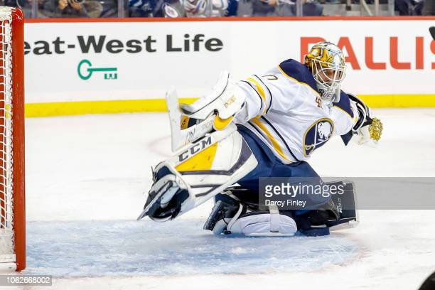 Goaltender Carter Hutton of the Buffalo Sabres stretches across the crease as the puck flies over his stick on a shot by Kyle Connor of the Winnipeg...