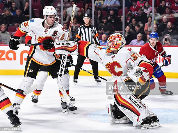Goaltender Chad Johnson makes a blocker save near teammate Sean Monahan of the Calgary Flames during the NHL game against the Montreal Canadiens at...
