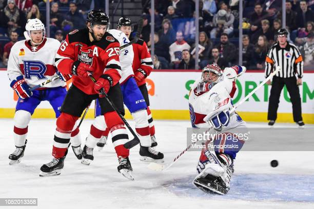 Goaltender Charlie Lindgren of the Laval Rocket makes a save in front of Eric Tangradi of the Binghamton Devils during the AHL game at Place Bell on...