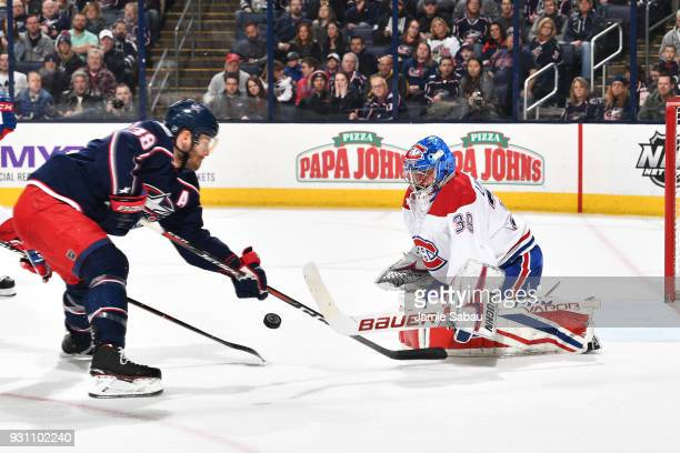 Goaltender Charlie Lindgren of the Montreal Canadiens knocks the puck away from Boone Jenner of the Columbus Blue Jackets during the first period of...