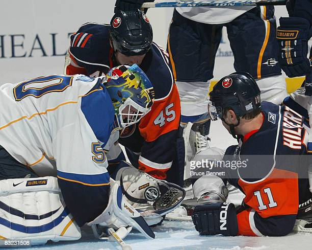 Goaltender Chris Mason of the St Louis Blues grabs the puck as Nate Thompson and Andy Hilbert of the New York Islanders wait for the rebound on...