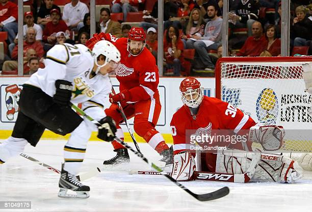 Goaltender Chris Osgood and Brad Stuart of the Detroit Red Wings protect the net as Loui Eriksson of the Dallas Stars skates in with the puck during...