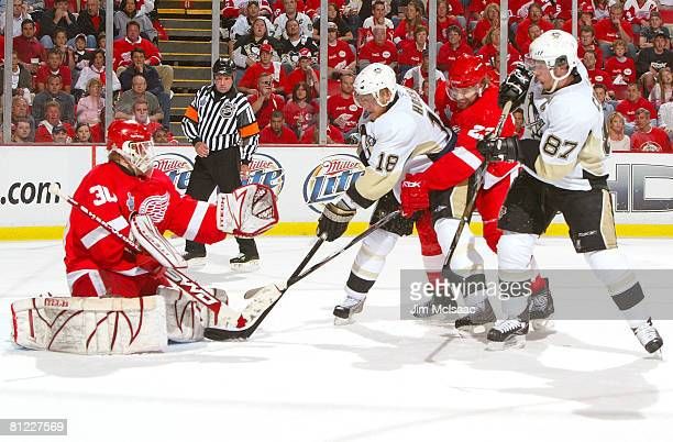 Goaltender Chris Osgood and Brad Stuart of the Detroit Red Wings defend the goal against Marian Hossa and Sidney Crosby of the Pittsburgh Penguins...